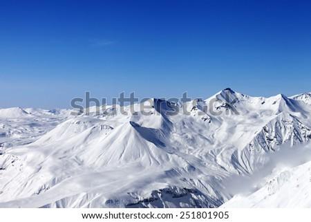 Snow mountains and blue clear sky. Caucasus Mountains, Georgia. View from ski resort Gudauri. - stock photo