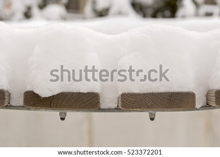 snow on a brown wooden bench in the yard