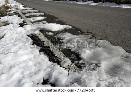 snow on asphalt road hide the white lines - stock photo