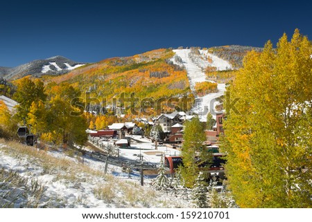 Snow on Golden Aspen Trees at Beaver Creek Resort, in Colorado with Ski Slopes and Gondola in Foreground - stock photo