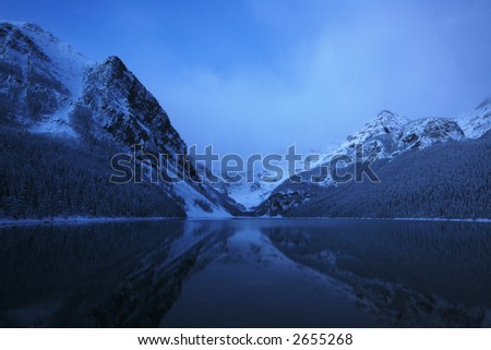 SNOW ON LAKE LOUISE AT NIGHT, VERY EARLY MORNING SUNRISE WITH THE MOUNTAINS REFLECTING IN THE LAKE - stock photo