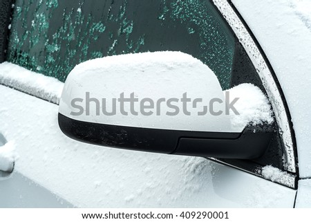 snow on side window of the white car - stock photo