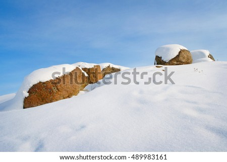 snow on the boulders and on the hill