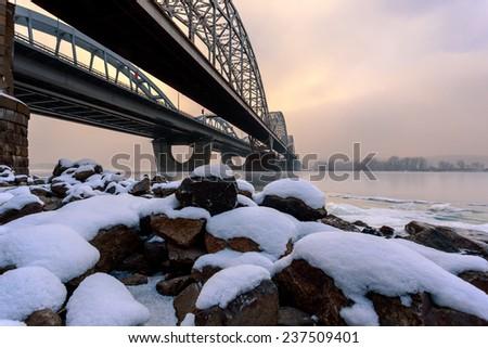 Snow on the river stones at the bank of the Dnieper river in Kiev. Near the Darnitsky bridge. - stock photo