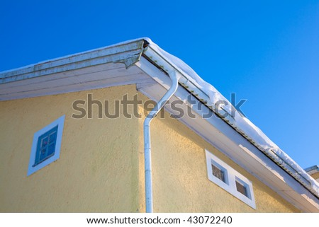 snow on the roof of a house - stock photo
