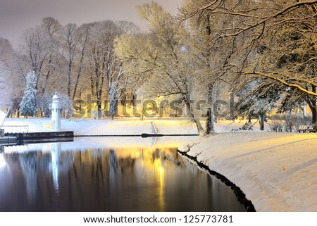 snow on trees in Riga park and lighthouse - stock photo