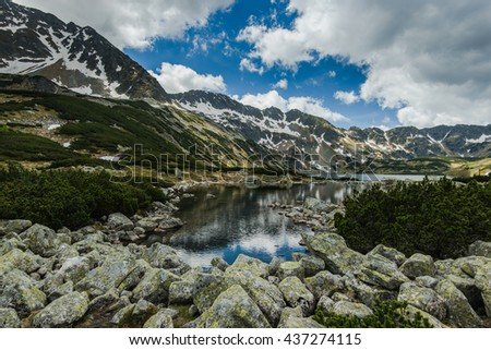 snow patches over high peak mountains in Tatra,Poland. Reflection in cristal clear water in lake. - stock photo