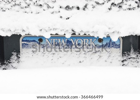 Snow piles up on a car bumper over (New York State) license plate - stock photo