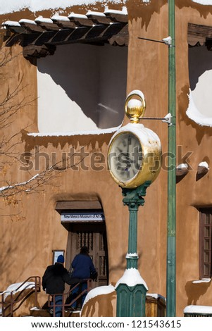 Snow piles up on Santa Fe's vigas and adobe walls in winter - stock photo