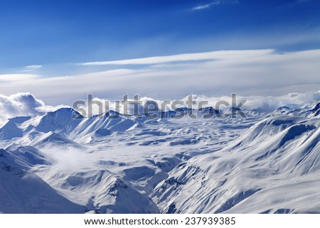 Snow plateau and sky with clouds. Caucasus Mountains, Georgia. View from ski resort Gudauri. - stock photo