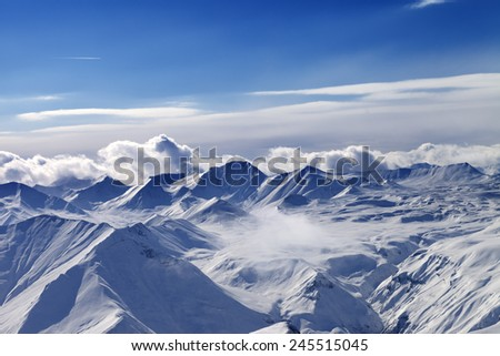 Snow plateau and sunlight sky with clouds in evening. Caucasus Mountains, Georgia. View from ski resort Gudauri. - stock photo