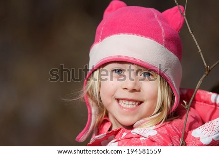 Snow Princess  Close-up of a happy little girl outside in her pink winter coat and hat. - stock photo