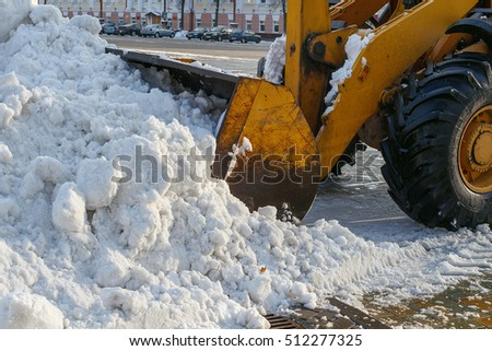 Snow removal equipment works in the city. Snow removal after a snowfall. Orange tractor with bucket loads of snow. Outdoors.