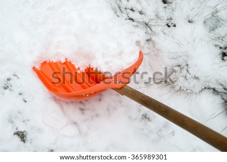 Snow removal. Orange Shovel in snow, ready for snow removal, outdoors.  - stock photo