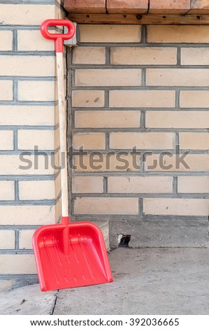 Snow removal. Red plastic Shovel, ready for snow removal, outdoors.  - stock photo