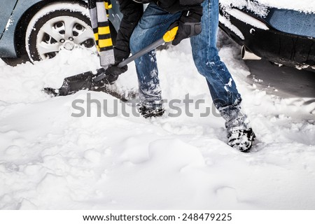 Snow removal with shovel and car in background - stock photo