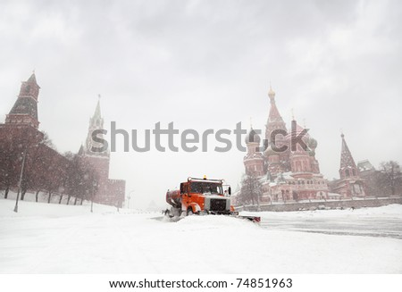 Snow-remover truck clean the road near Red Square, St Basil Temple and Spasskaya Tower of Kremlin in Moscow, Russia at wintertime during snowfall - stock photo