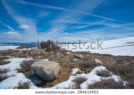 Snow rocks boulders and shrubs on a mountain peak in California mountains. - stock photo