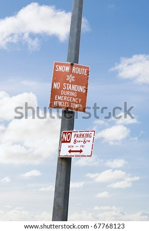 snow route sign and no parking sign mounted on the column against the blue sky - stock photo
