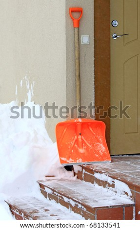 Snow shovel standing on the steps beside front door - stock photo