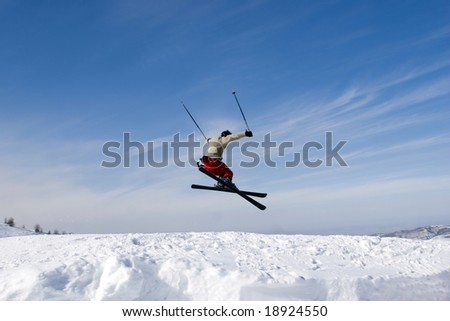 Snow Skier Jumping Against Blue Sky - stock photo