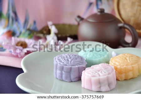 Snow skin mooncake on plate with teapot on pink background - stock photo