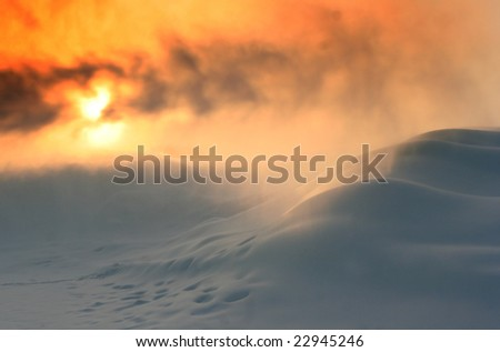 Snow snowstorm with snow drifts against a rising sun.