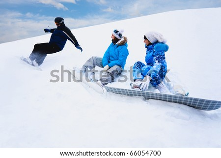 Snow splashes from board and two young girls sit on the bottom of the mountain - stock photo