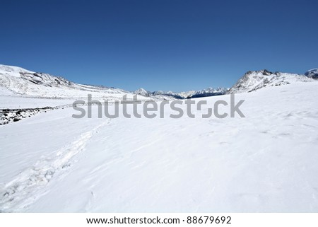 Snow surface of mountains against the blue sky . Elbrus area. Caucasus mountains. - stock photo