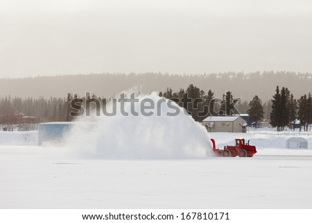 Snow thrower truck clearing road after whiteout winter snowstorm blizzard for vehicle access - stock photo