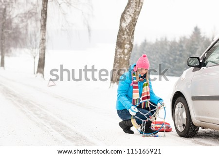 Snow tire chains winter car woman in trouble breakdown - stock photo