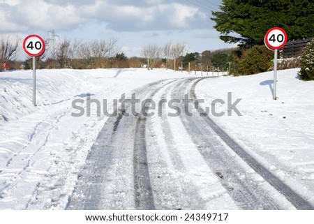 Snow tracks on a country road and 40 mph signs. - stock photo