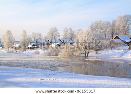 snow village on coast river - stock photo