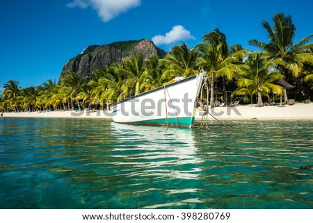 snow-white fishing boat parked in the clear emerald ocean on a background of high mountains and palm trees. Indian Ocean, Mauritius island - stock photo