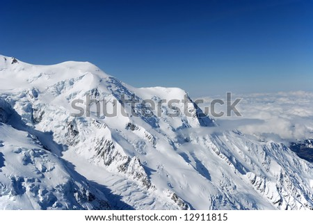 Snow white mountain peaks and blue sky above stratum of fluffy clouds covered land, Alps, Mont Blanc