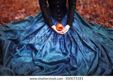 Snow White princess with the famous red apple. Girl holds a ripe Apple sitting on lap