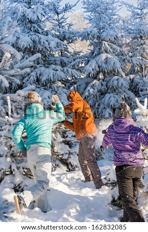 Snowball fight winter friends having fun playing in snow outdoors - stock photo
