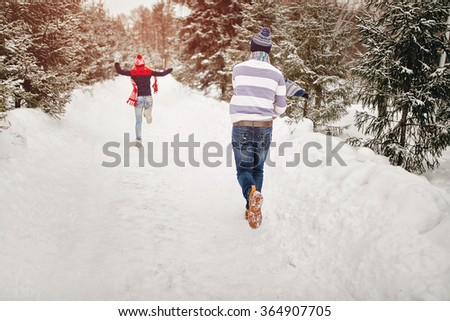 Snowball fight. Winter loving couple having fun playing catch up outdoors. Young joyful happy couple in love - stock photo