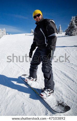 Snowboard beginner enjoys a snow slope ride - stock photo