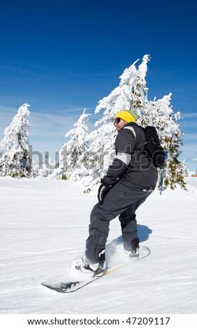 Snowboard beginner  on a snow slope riding his snowboard. - stock photo