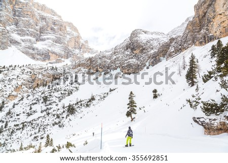 Snowboard freerider in the mountains along the mighty Dolomite cliffs. - stock photo