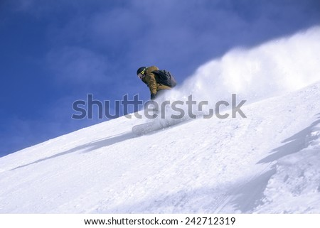 Snowboard freerider in the mountains with blue sky in the background