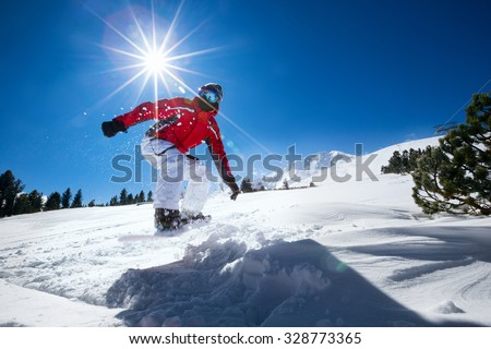 Snowboard in the mountains jumping through air - stock photo