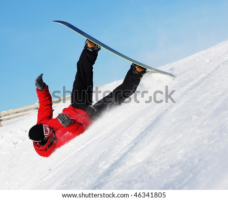 Snowboard sportsmen in fall over clear blue sky - stock photo
