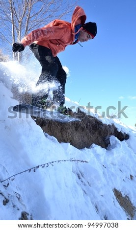 Snowboarder at jump inhigh mountains at sunny day. - stock photo