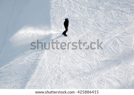 Snowboarder carving down the slope  - stock photo
