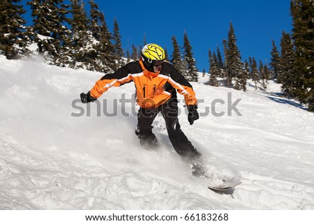 Snowboarder doing a toe side carve with deep blue sky in background - stock photo