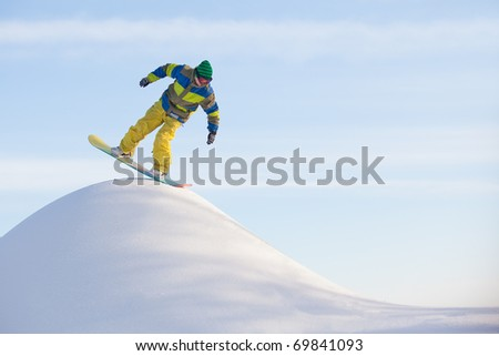 snowboarder doing a trick on the snow pile - stock photo