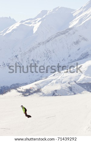 Snowboarder down hill in winter snow mountain landscape. France. Alps. - stock photo