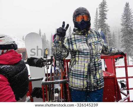 snowboarder during a snowfall, stands on the snowcat, before getting on top of the mountain